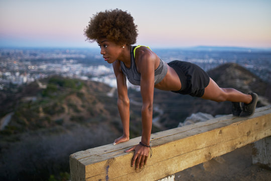athletic african american woman working out doing pushups on bench at runyon canyon