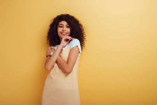 cheerful bi-racial girl holding hand near face while looking at camera on yellow background
