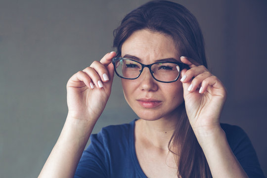 A woman with vision problems hold eyeglasses