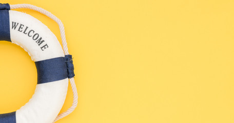 Lifebuoy with the word welcome on a yellow background. Time for summer vacation, conceptual photo with empty space.