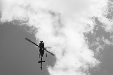 black and white picture of helicopter flying through the sky