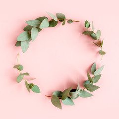 Wall Mural - Wreath made of branches eucalyptus, leaves isolated on pink background.  Flat lay, top view. floral concept