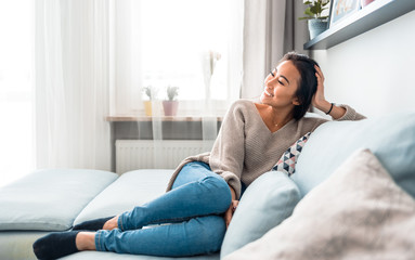 Fotorolgordijn Ontspanning Relaxed smiling asian woman sitting on sofa at home