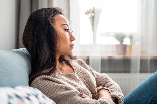 Sad asian girl sitting on sofa at home and thinking