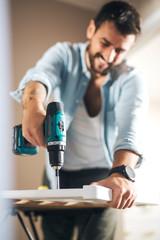 Close up of a man holding a screwing machine.