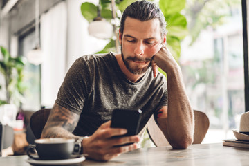 Handsome bearded hipster man use smartphone with coffee at table in cafe.Communication and technology concept Papier Peint
