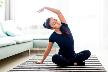 Young asian girl exercising at home on carpet in living room Fotomurales