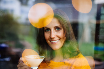 Young woman drinking tea or coffee thoughtfully in a cafe behind a glass window