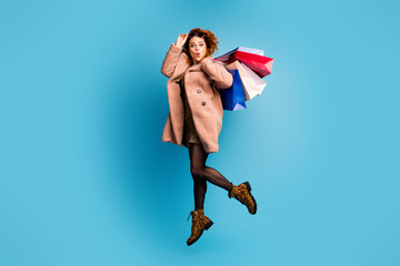 Full body photo of crazy astonished woman look boutique bargain impressed jump scream wow omg wear beige outerwear feminine beautiful tights boots isolated over blue color background