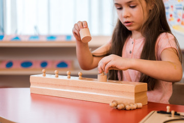Child playing wooden educational game in montessori school