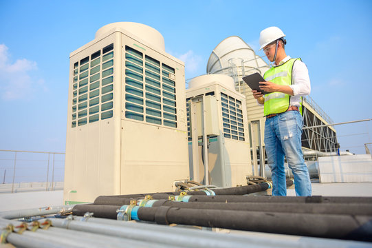 Engineer check condition cooling tower project at industry by tablets, measuring equipment for filling air conditioners.