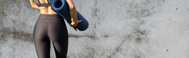 A sporty slim girl in leggings and a top is standing near a concrete wall with a training mat,...