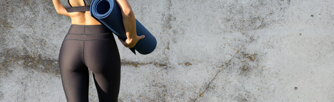 A sporty slim girl in leggings and a top is standing near a concrete wall with a training mat, resting between exercises.