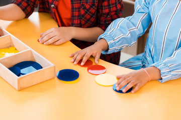 Cropped view of kids folding colorful game on table in montessori school