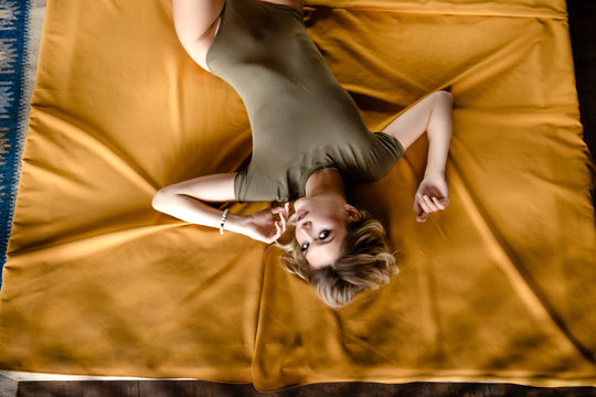 Top view of a young beautiful blonde woman with bright make-up and bodysuit in a studio. A girl lying on a yellow bed. Upside down photo