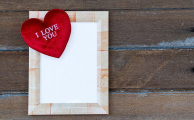 Square picture frame with a red heart resting on a frame. In the heart there is a message that I love you. All of this is laid on an old wooden plate.