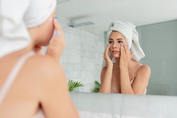 Young woman applying anti-wrinkle eye cream standing behind mirror in home bathroom. Beautiful girl wearing bath towel on head portrait. Cosmetology and beauty procedure. Skin care after cleansing Fotomurales