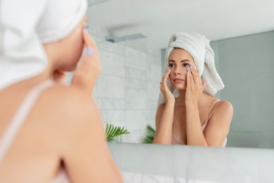 Young woman applying anti-wrinkle eye cream standing behind mirror in home bathroom. Beautiful girl wearing bath towel on head portrait. Cosmetology and beauty procedure. Skin care after cleansing