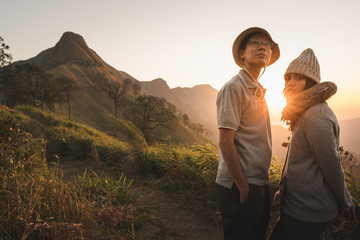 Young couple looking at the sunrise over the mountain