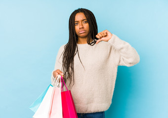 Young african american woman holding a shopping bag isolated showing a dislike gesture, thumbs down. Disagreement concept.