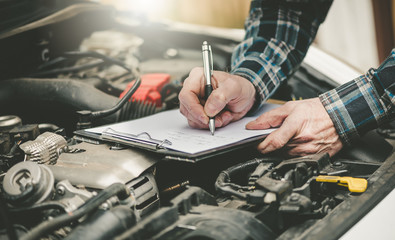 Car mechanic checking a car engine Fotomurales