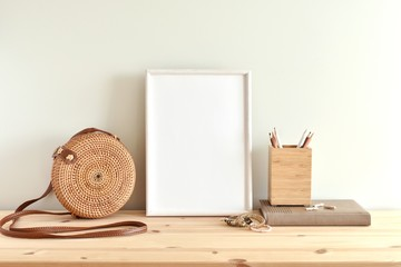 White blank frame mockup for poster or photo on wooden shelf, round rattan bag, boho style bracelets.