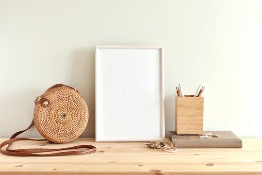 White blank frame mockup for poster or photo on wooden shelf, round rattan bag, boho style bracelets.