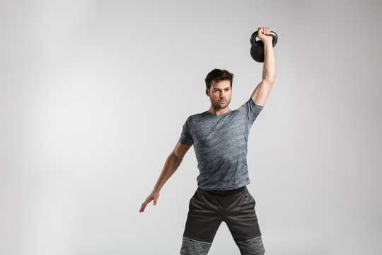 Image of young strong man doing exercise with weight while working out