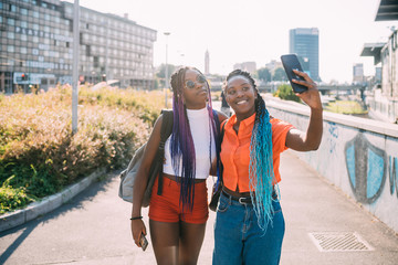 Young beautiful black sisters outdoor backlight using smartphone taking selfie