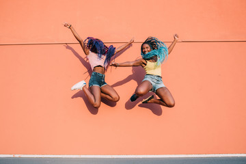 Two young beautiful black women outdoor jumping spreading arms having fun