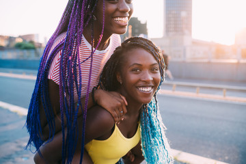 Portrait of two sisters black women outdoor having fun hugging riding piggyback
