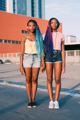 Two young beautiful black sisters holding hands listening music posing