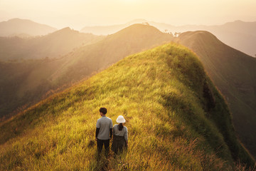 Young couple over the green mountain at sunset