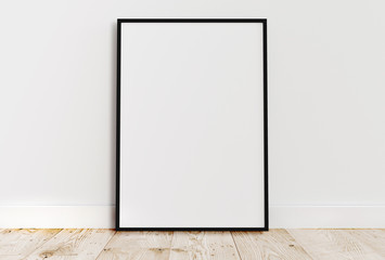 Blank vertical black poster frame standing on light wooden floor with next to white wall. Blank poster frame mockup. Empty picture frame mockup. Vertical frame mock up. Blank photo frame. 3d rendering