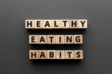 Healthy Eating Habits - words from wooden blocks with letters, healthy eating habits concept, top view gray background