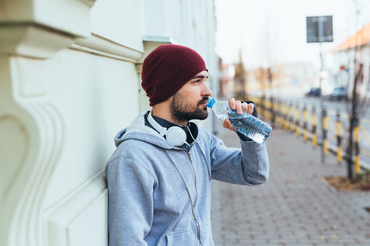 handsome young man jogging outdoors. drinking water