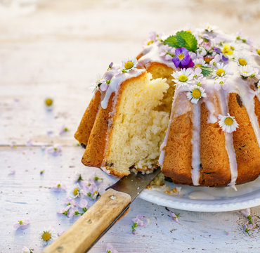 Easter yeast cake (Babka) covered with icing and decorated with edible flowers on a white plate on a white wooden table, close-up. Traditional Easter cake in Poland