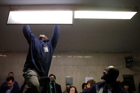 Building maintenance workers change a light bulb as reporters wait to enter the courtroom to listen to the case against film producer Harvey Weinstein at New York Criminal Court during the sexual assault trial in the Manhattan borough of New York City, New