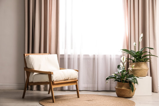 Comfortable armchair near window with elegant curtains in room