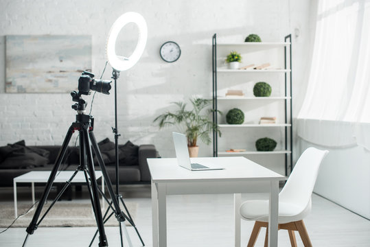 digital camera on tripod near ring lamp and table with laptop