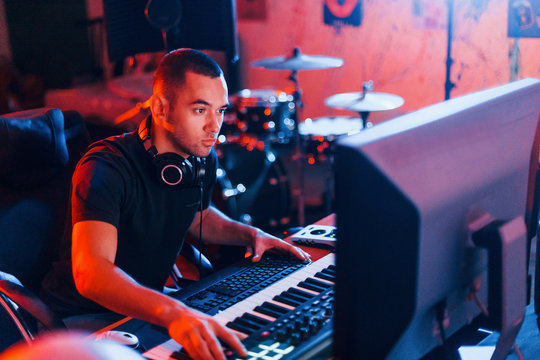 Sound engineer working and mixing music indoors in the studio
