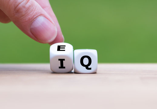 """Hand turns a dice and changes the expression """"IQ"""" (Intelligence Quotient) to """"EQ"""" (Emotional Intelligence/Quotient)."""