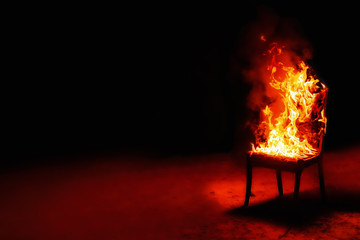 Burning chair on a black background. Conceptual photo burnout at work. Place for an inscription.