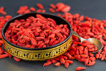 Goji berry in gold east bowl in close-up. Selective focus