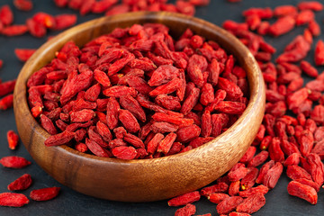Goji berries in wooden cup. View from above, selective focus