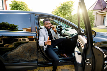 Successful handsome African man businessman and boss sitting in the car, talking on the phone, smiling, looking at camera and showing thumb up. Business concept