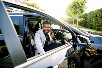Happy smiling African american businessman in smart casual suit speaking on smartphone while getting in the black car on passenger seat.