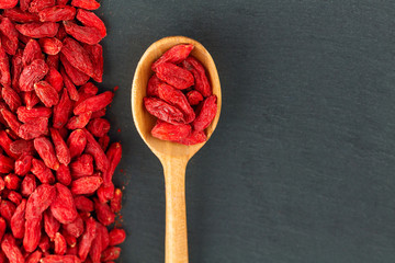 Goji berries. Spoon with organic berry over gray slate background
