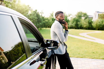 African american businessman in a suit speaking on smartphone while standing outdoors near his luxury black car. Green park, trees on the background