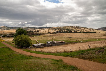 Richmond, Tasmania, Australia - December 13, 2009: Rural landscape with farm under heavy gray cloudscape of forested hills, dirt road, and dry meadows. Corrugated roofs on barns.